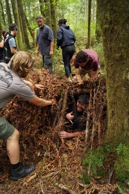 Students building a debris hut shelter